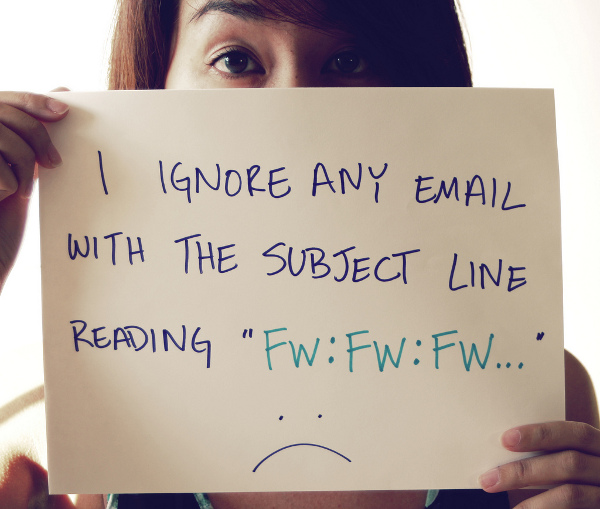 "Woman holding a sign that reads ""I ignore any email with the subject line reading ""FW:FW:FW..."""". Beneath the text is an unhappy face"